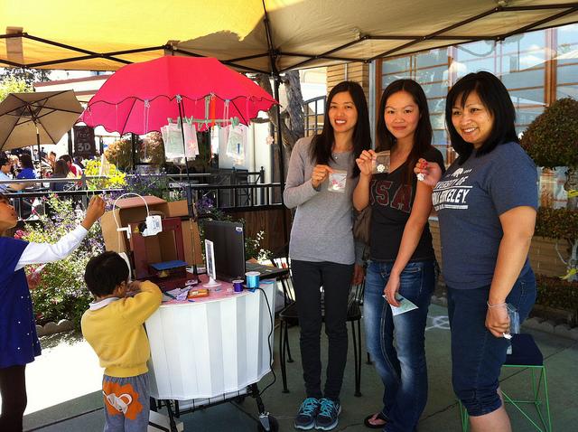 Three women proudly display their netsuke.